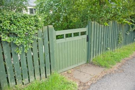 Use of muted color value on a green garden fence