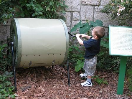child turning a soil composter