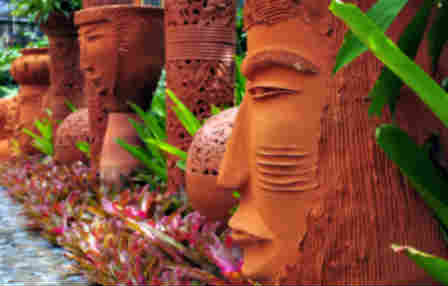 clay tiki heads used as a decorative garden accent