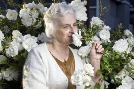 photo of an older woman smelling the roses