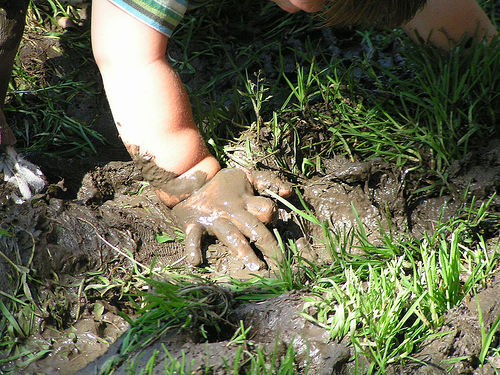 a small child plays in muddy ground
